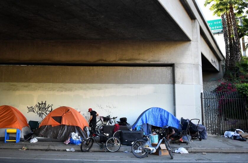 Homeless people line up tents along Figueroa St. under the 101 Freeway