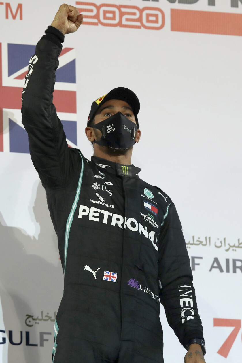 FILE - In this Sunday, Nov. 29, 2020 file photo Mercedes driver Lewis Hamilton of Britain celebrates after wining the Formula One race in Bahrain International Circuit in Sakhir, Bahrain. World champion Lewis Hamilton tested positive for COVID-19 and will miss the Sakhir Grand Prix this weekend, his Mercedes-AMG Petronas F1 Team said Tuesday Dec. 1, 2020. (Tolga Bozoglu, Pool via AP, File)