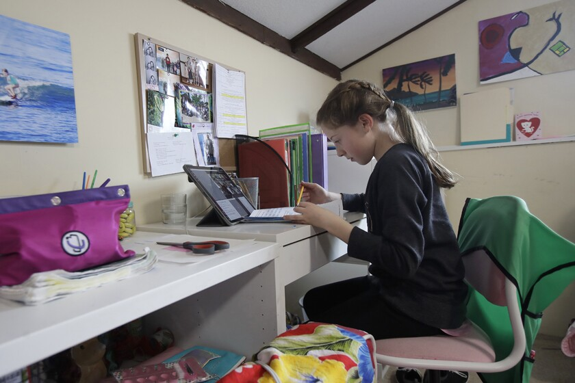 A student attends class via a laptop at her home in San Francisco.