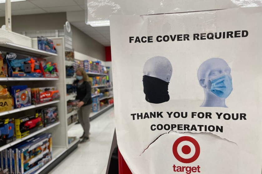LOS ANGELES, CA - MAY 17: Signage inside Target reads that there is a mask mandate on the first day it has dropped the requirement for fully vaccinated customers, joining with Walmart, Trader Joes, Starbucks, Costco and other businesses in downtown on Monday, May 17, 2021 in Los Angeles, CA. (Dania Maxwell / Los Angeles Times)