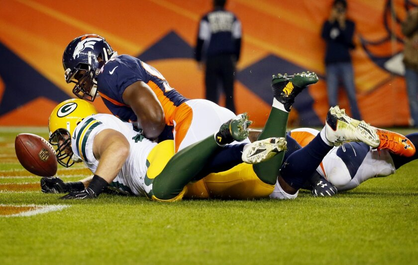 Denver Broncos outside linebacker DeMarcus Ware, top, chases down the football in the end zone for a safety with Green Bay Packers fullback John Kuhn during the second half of an NFL football game, Sunday, Nov. 1, 2015, in Denver. (AP Photo/Jack Dempsey)