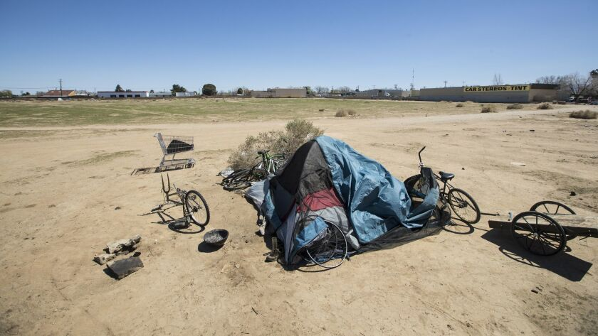 A tent is surrounded by bicycles in various states of disrepair on a vacant lot in Lancaster.