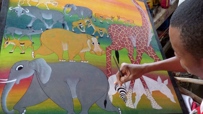 TANZANIA - Tinga Tinga artist Hasin White at work in a roadside shop outside Tarangire National Park