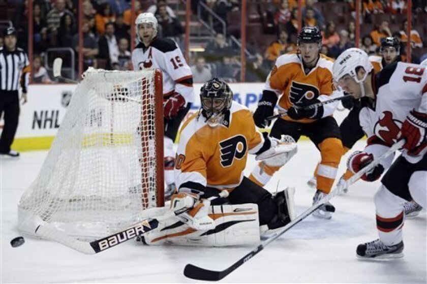 Philadelphia Flyers' Ilya Bryzgalov (30), of Russia, deflects a shot as New Jersey Devils' Steve Bernier (18) looks for the rebound in the first period of an NHL hockey game, Thursday, April 18, 2013, in Philadelphia. (AP Photo/Matt Slocum)