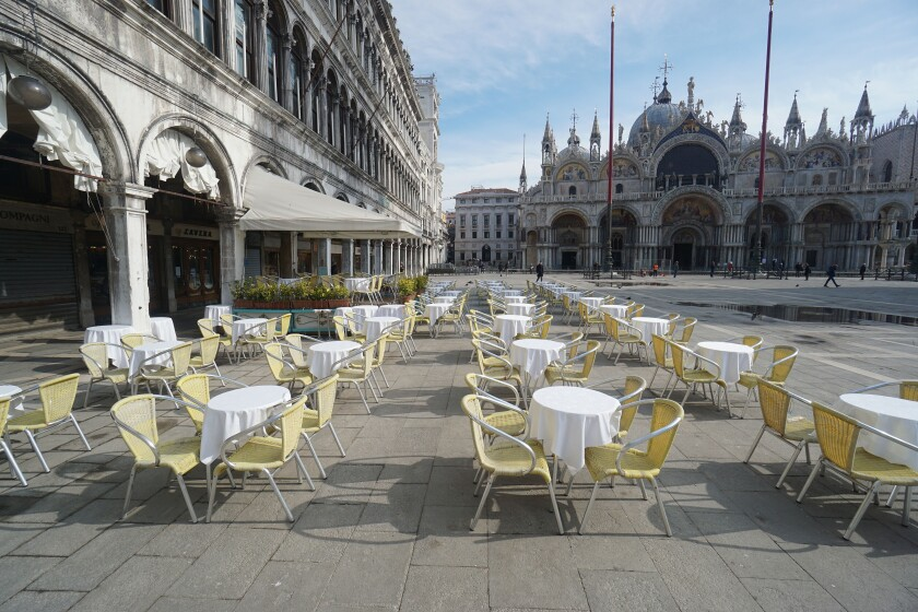 Empty chairs and tables are lined up outside a restaurant in St. Mark's Square in Venice, Italy, on Monday. A similar fate may await restaurants, bars, and sports and entertainment venues in America.