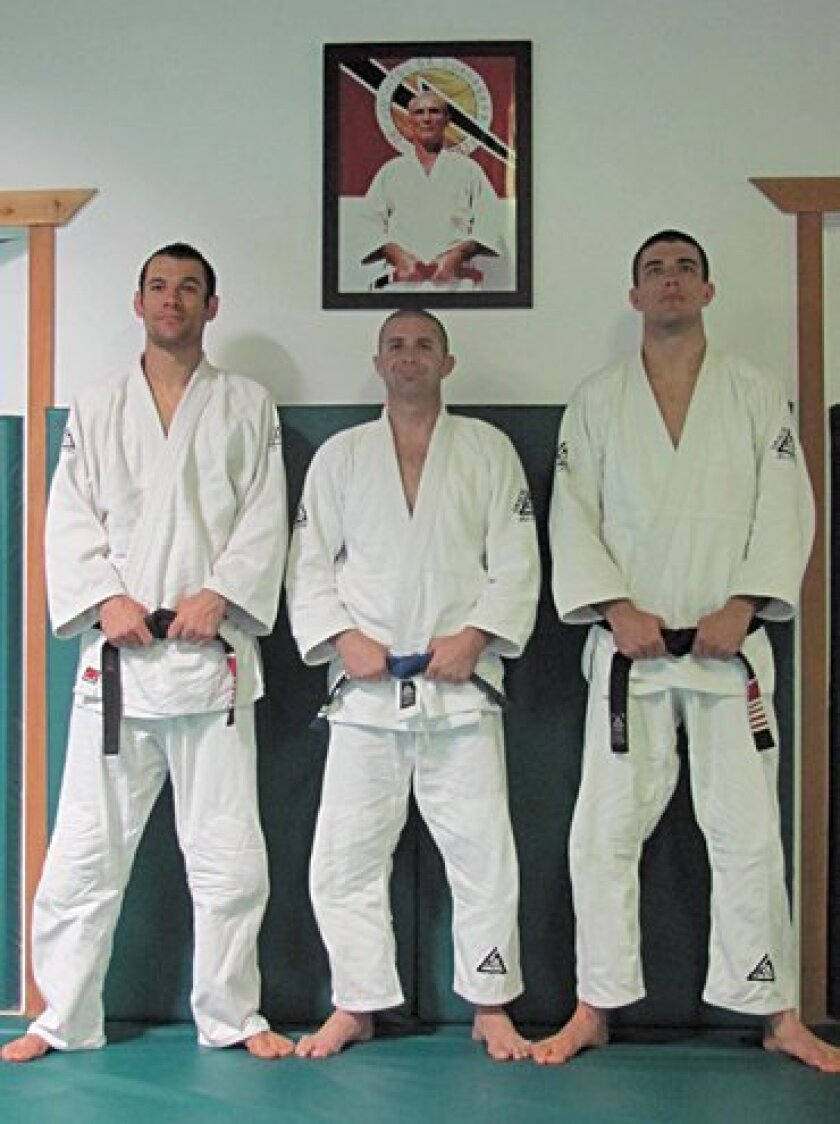 Ryron Gracie, Matthew Becker and Rener Gracie with the image of Helio Gracie in the framed photo