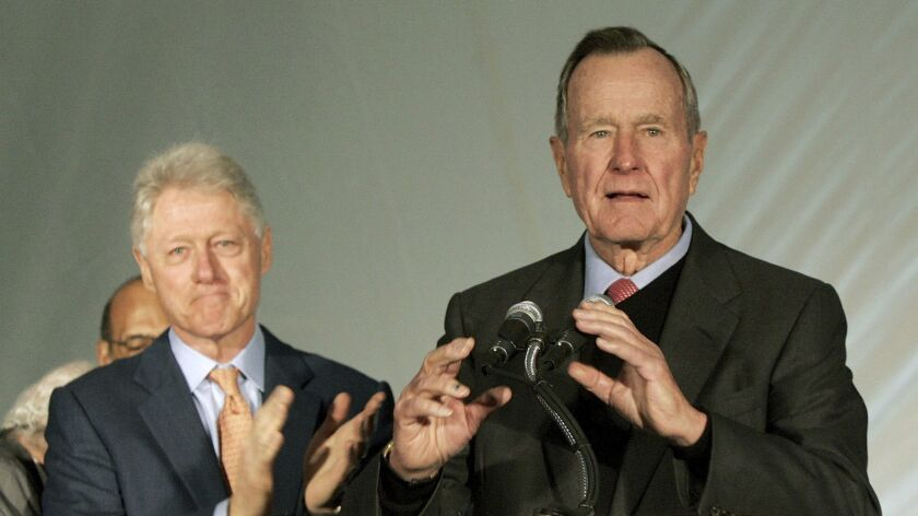 Former Presidents Bill Clinton, left, and George H.W. Bush appear together during a news conference where they spoke about money they raised for Hurricane Karina victims on Dec. 7, 2005.