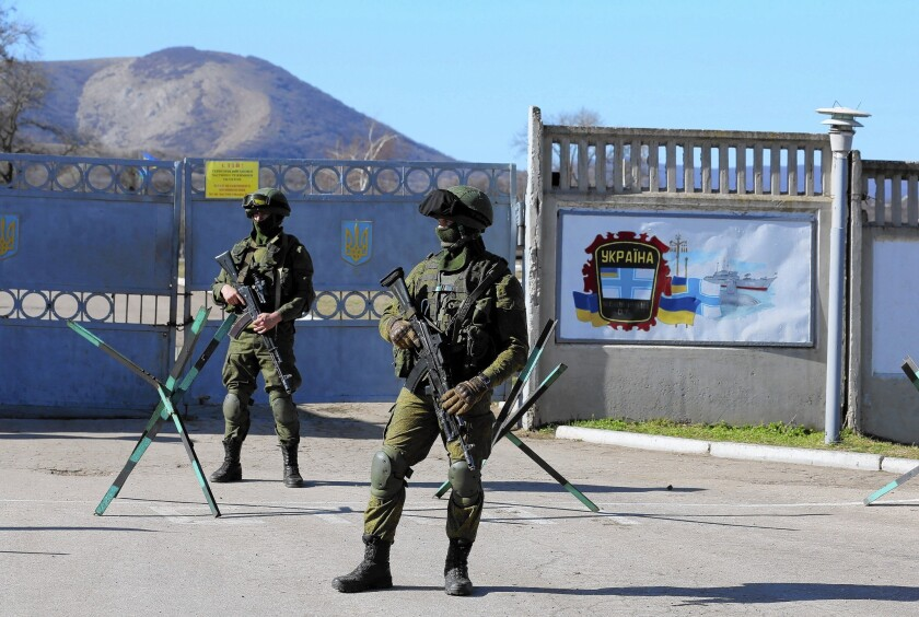 Russian soldiers stand outside a Ukrainian military base in Perevalnaya, in Ukraine's Crimea region. The facility, under siege by Russian forces for three days, faced demands that it give up its weapons.