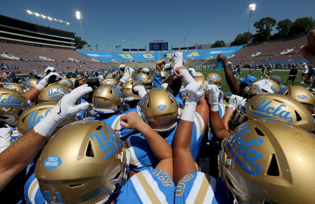 UCLA players huddle before playing Hawaii at the Rose Bowl.
