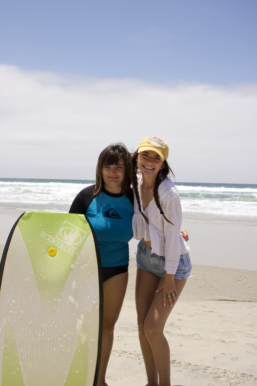 Mia Boggs at right with Sabrina, one of the students at the Sunshine Surf Camp that Mia created.