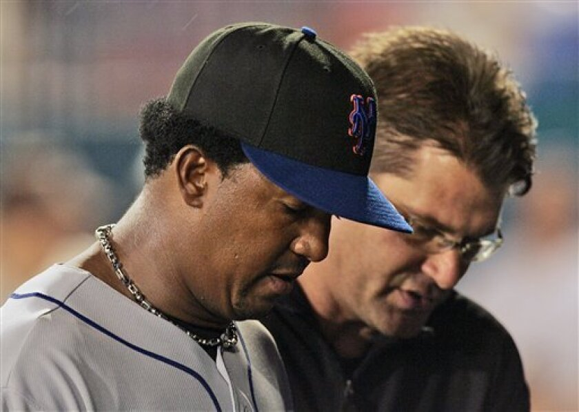 New York Mets starting pitcher Pedro Martinez, left, is escorted off the field after getting injured during the fourth inning of a baseball game against the Florida Marlins, Tuesday, April 1, 2008, in Miami. (AP Photo/J. Pat Carter)