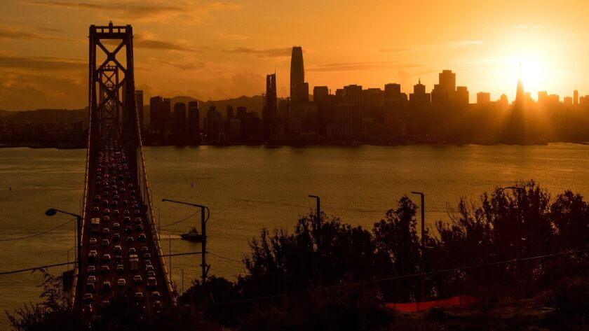 Traffic moves along the Bay Bridge as the sun sets behind the Transamerica Pyramid in San Francisco, once the tallest building on the city's skyline.