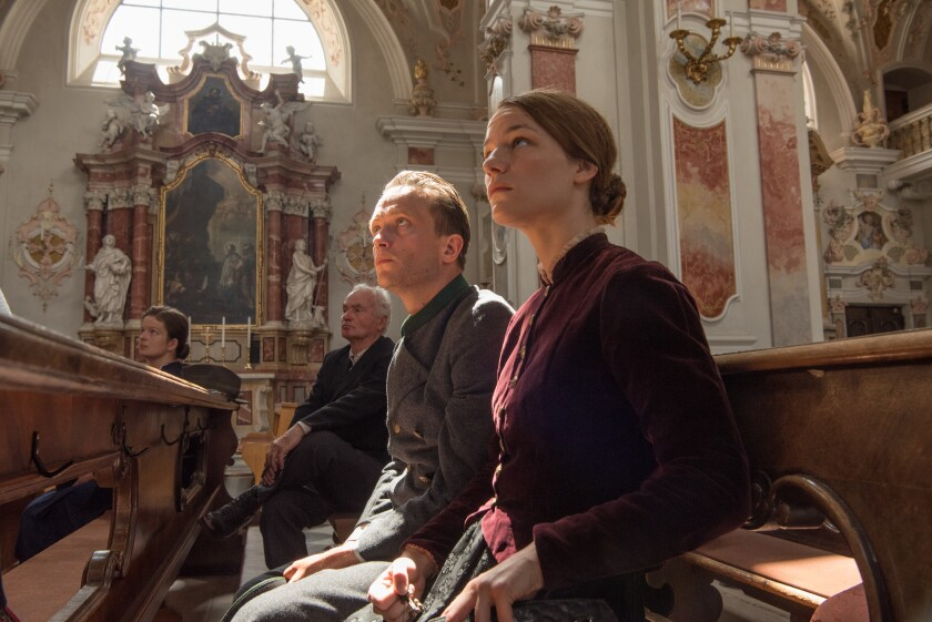 """August Diehl, Valerie Pachner and another man and woman sit in the pews of a church in """"A Hidden Life."""""""