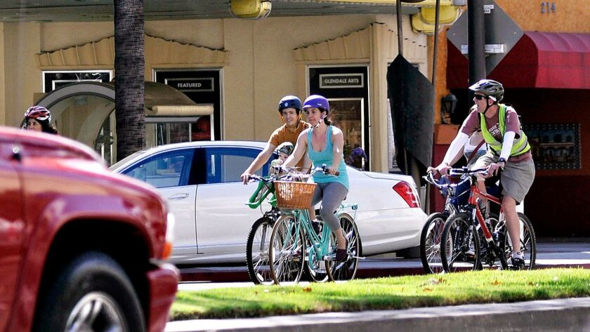 Cyclists ride past the Alex Theatre in Glendale.