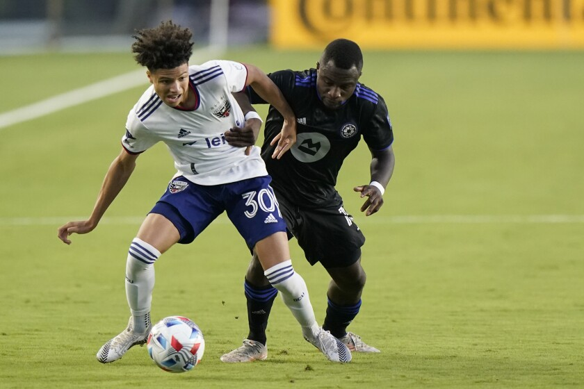 D.C. United midfielder Kevin Paredes (30) and CF Montreal defender Zachary Brault-Guillard battle for the ball, Wednesday, June 23, 2021, during the first half of an MLS soccer match in Fort Lauderdale, Fla. (AP Photo/Wilfredo Lee)