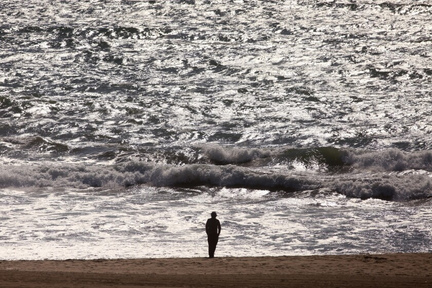 A lone person practices tai chi at Venice Beach, with fewer people out than usual in light of the coronavirus threat.