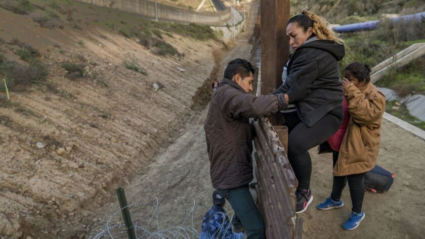 A pregnant migrant climbs the border fence before jumping into the U.S. to San Diego, Calif., from T