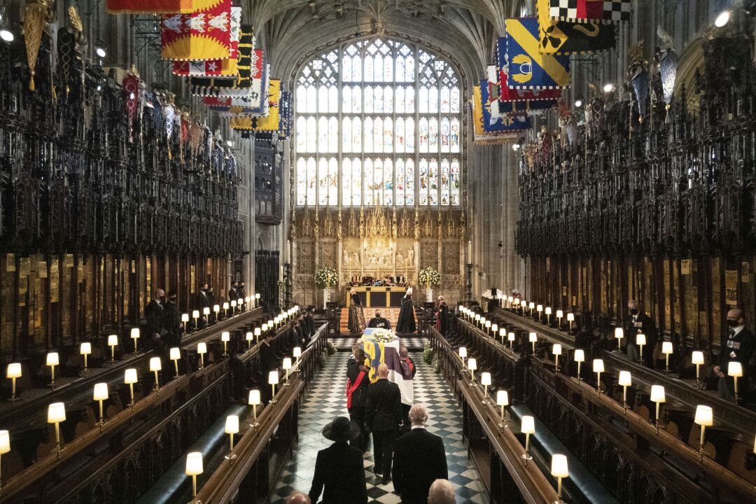 The coffin is carried by pallbearers followed by mourners in St. George's Chapel past pews with a few people in them.