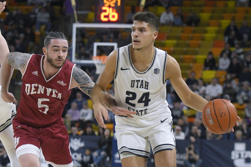 Utah State guard Diogo Brito (24) dribbles the ball as Denver guard Ray Kowalski (5) defends during the first half of an NCAA college basketball game Tuesday, Nov. 12, 2019, in Logan, Utah. (AP Photo/Eli Lucero)