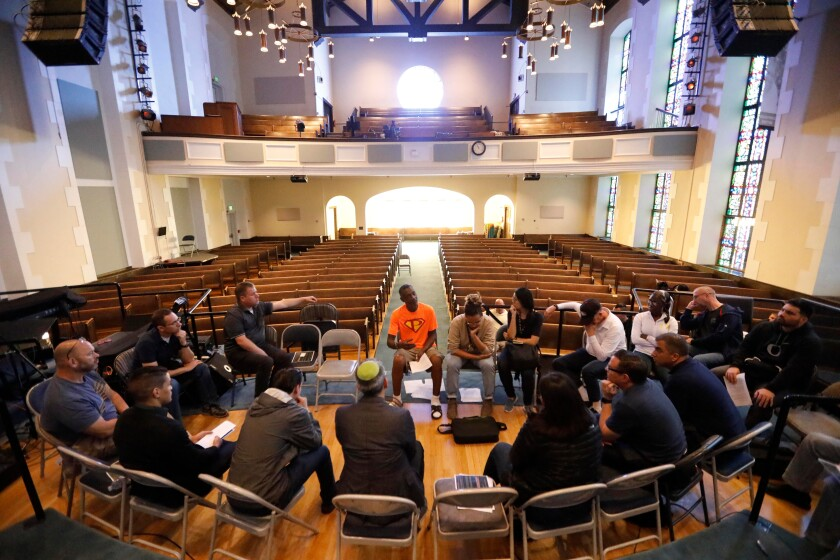 People sit in chairs in a circle inside a church.