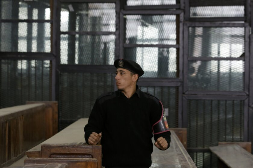 An Egyptian policeman guards the courtroom defendant's cage during the verdict hearing in a case rooted in violence that swept the country after the military-led ouster of Islamist President Mohammed Morsi in 2013, in Cairo, Egypt, Saturday, April 11, 2015. Egypt's official news agency said the court upheld death sentences for 14 people, including the leader of the country's banned Muslim Brotherhood, and sentenced 37 others to life in prison. US-Egyptian citizen Mohammed Soltan, who has been on hunger strike for more than 14 months as his health deteriorates, is one of the defendants handed a life sentence on Saturday on charges of financing an anti-government sit-in and spreading false news. (AP Photo/Hassan Ammar)
