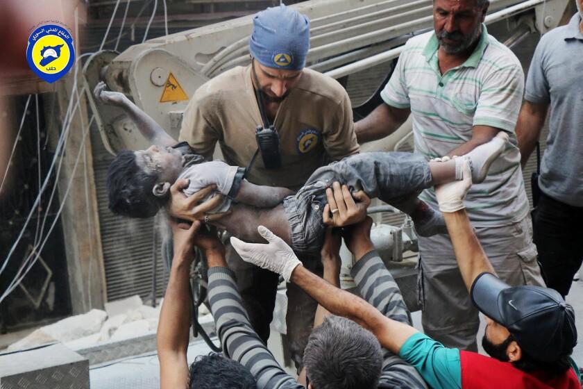 Esta foto del martes 27 de septiembre del 2016, provista por el grupo de defensa civil siria conocido como Cascos Blancos, muestra a socorristas cargando el cuerpo de un niño luego que ataques aéreos impactaran el vecindario de al-Shaar, en Alepo, Siria.