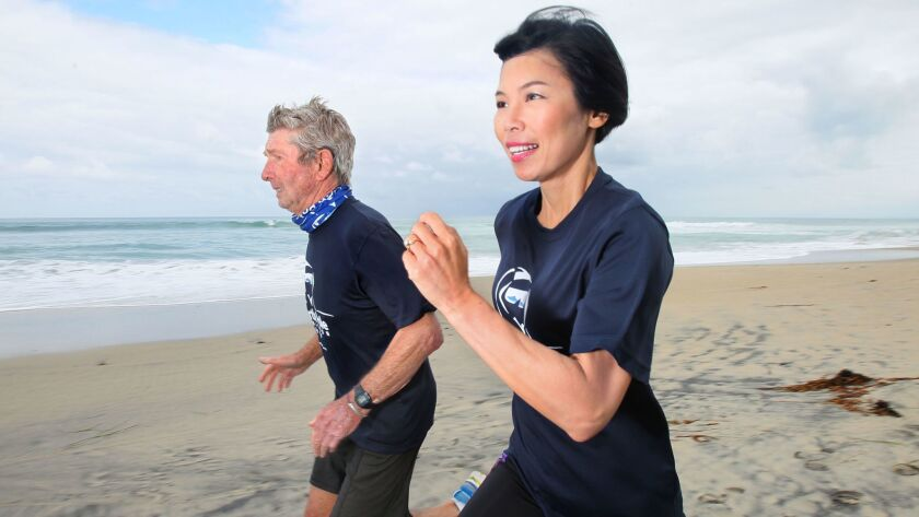 Marathon runners Michel Ribet, left, and Vivian Lee go for a training run on the beach in Del Mar.