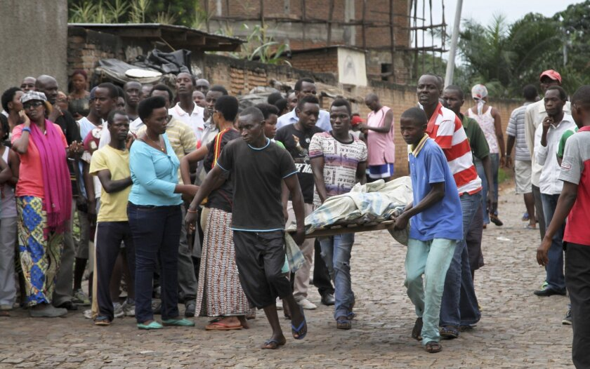 Men carry away a dead body in the Nyakabiga neighborhood of Bujumbura, Burundi, Saturday, Dec. 12, 2015. Burundi's political violence continued Saturday as a number of people were found shot dead in the Nyakabiga neighborhood of the capital.