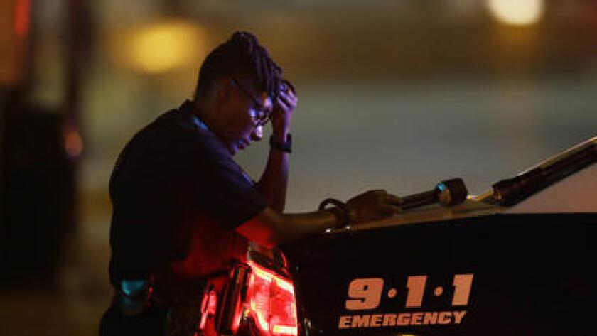 A Dallas police officer, who did not want to be identified, takes a moment as she guards an intersection after the deadly shooting.
