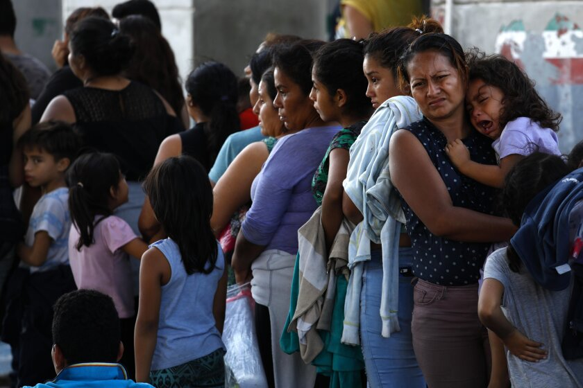 Asylum seekers wait in the parking lot of an immigration checkpoint in Nuevo Laredo, Mexico, on Aug. 1.