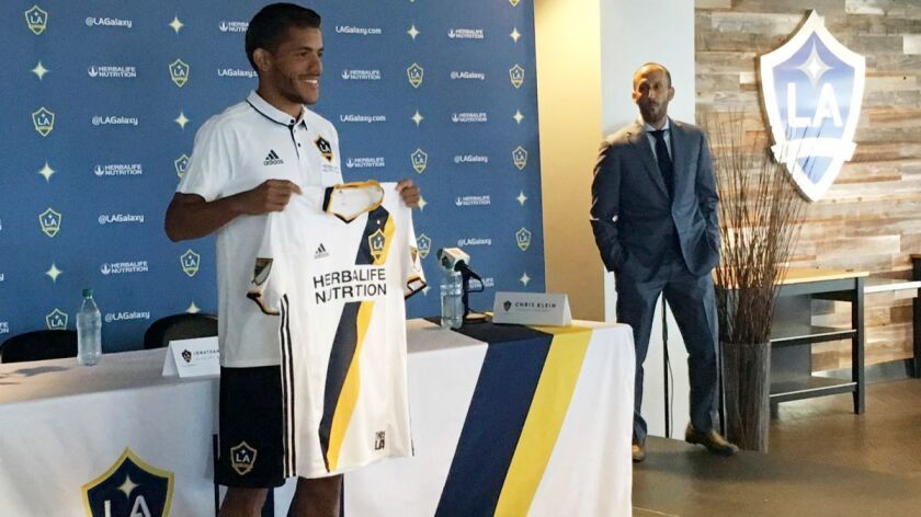 LA Galaxy's new player Jonathan dos Santos holds up a jersey following an MLS soccer press conferenc