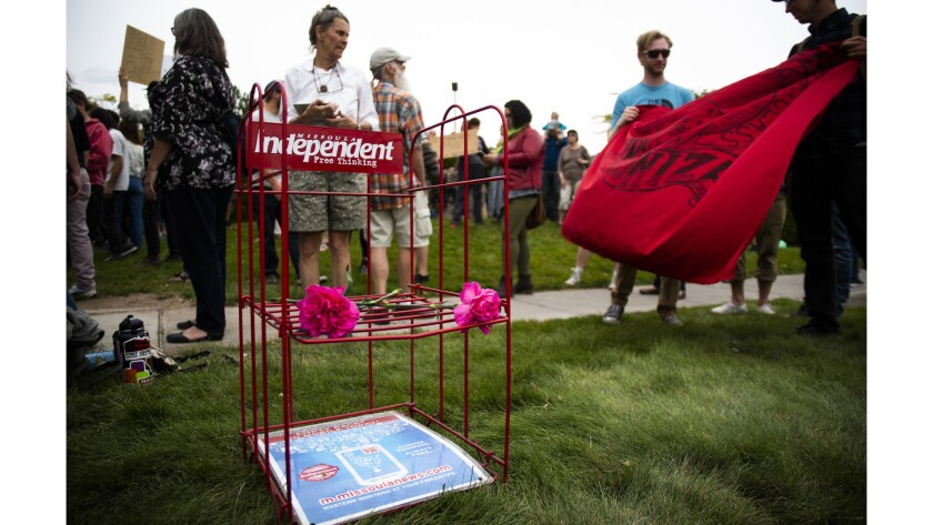 The almost-empty newstand of the Missoula Independent sits with roses, as protesters gather outside
