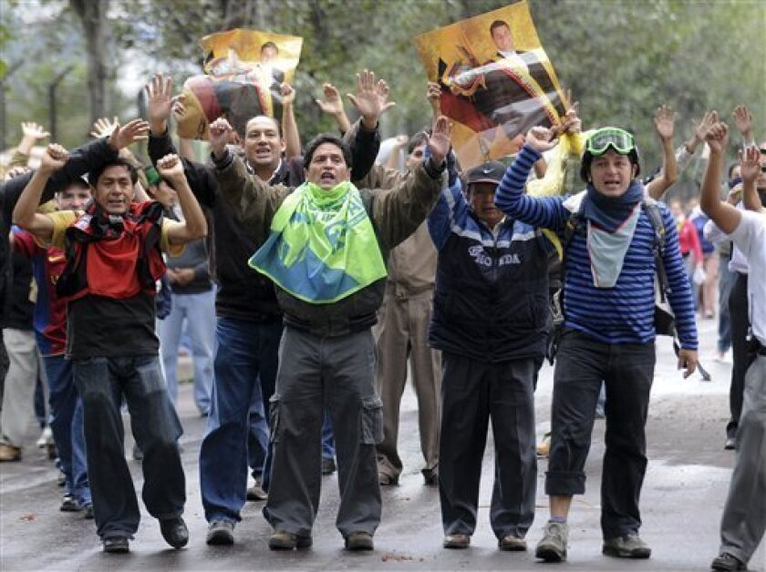 Supporters of Ecuador's President Rafael Correa, carrying posters of Correa, protest against rebellious police outside the hospital where Correa is located in Quito, Ecuador, Thursday Sept. 30, 2010.  The government declared a state of siege Thursday after rebellious police, angered by a law that c