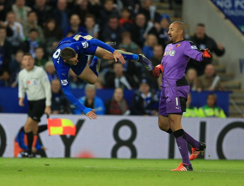Leicester City's Jamie Vardy, left, is awarded a penalty after being brought down by Watford goalkeeper Heurelho Gomes, during the English Premier League soccer match between Leicester and Watford, at King Power Stadium, in Leicester, England, Saturday, Nov. 7, 2015.  (Nigel French/PA via AP) UNITE