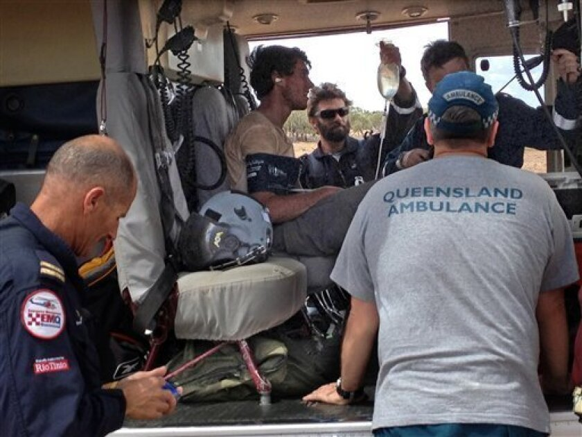 In this Feb. 15, 2013 photo, British backpacker Sam Derry-Woodhead, second left, sits in a rescue helicopter as he is tended to by ambulance personnel, near Upshot Station, a cattle ranch 90 kilometers (55 miles) from Longreach, Australia. Derry-Woodhead, 18, drank contact lens fluid and his own urine to survive three days lost in Australian Outback scrubland in oppressive summer heat, his mother said Saturday. (AP Photo/Angus Emmott) EDITORIAL USE ONLY