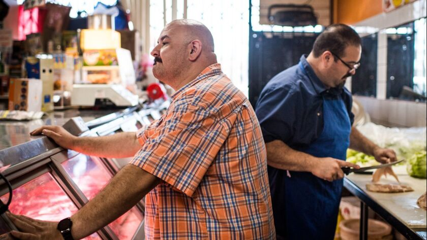 VAN NUYS, CA - Isaac Gonzalez tends to a customer while his brother Juan and co-owner of Carniceria