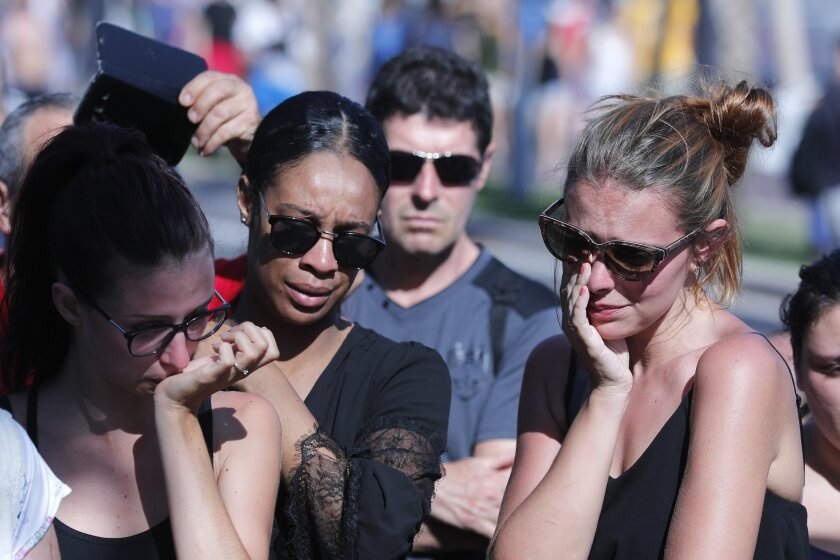 Women react near the scene where a truck mowed through revelers in Nice, southern France, Friday, July 15, 2016. A Tunisian living in France drove a large truck through crowds celebrating Bastille Day along Nice's beachfront, killing more than 80 people, many of them children, according to police and hospital officials. (AP Photo/Francois Mori)