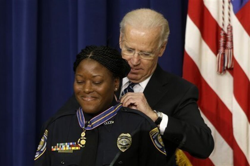 Vice President Joe Biden presents the Medal of Valor to Officer Reeshemah Taylor of the Osceola County Corrections Department in Florida., Wednesday, Feb. 20, 2013, during a ceremony in the Eisenhower Executive Office Building on the White House complex in Washington. The medal is the highest natio