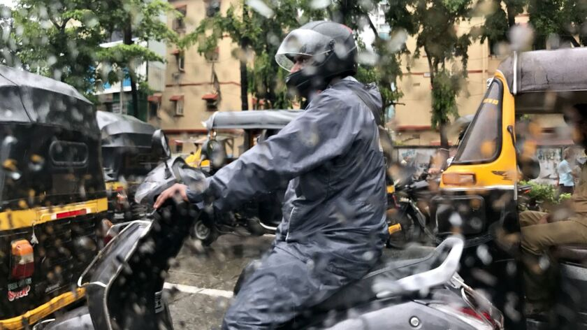 A motorcycle rider is dressed for the monsoon in Mumbai, India.