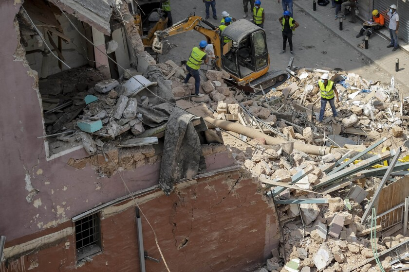 Rescuers search at the site of a collapsed building after getting signals there may be a survivor under the rubble.