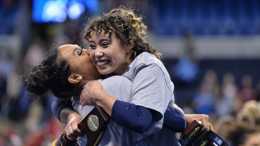 UCLA's Katelyn Ohashi and Peng-Peng Lee, left, celebrate after winning the NCAA women's gymnastics