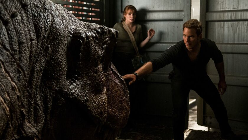 """(L-R) - Claire (BRYCE DALLAS HOWARD) and Owen (CHRIS PRATT) try not to wake the mighty T. rex in """"Ju"""