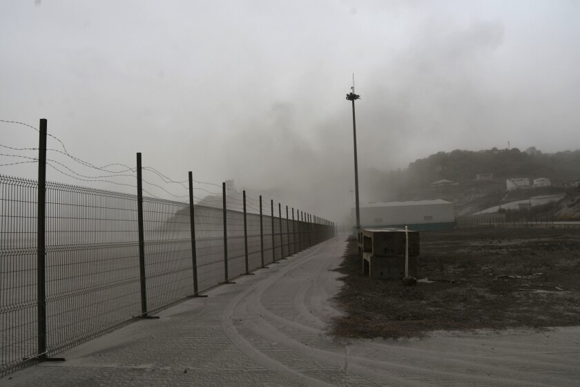 A road is blanketed in volcanic ash at the international airport in Kingstown, on the eastern Caribbean island of St. Vincent, Saturday, April 10, 2021 due to the eruption of La Soufriere volcano. (AP Photo/Orvil Samuel)