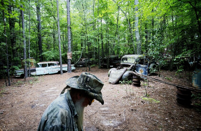 Eddie McDaniel, who goes by Fast Eddie, walks through Old Car City, the world's largest known classic car junkyard, where he occasionally plays piano for visitors Thursday, July 16, 2015, in White, Ga. Over 4,000 classic cars decorate 32 acres of forest which have been turned into a junkyard museum