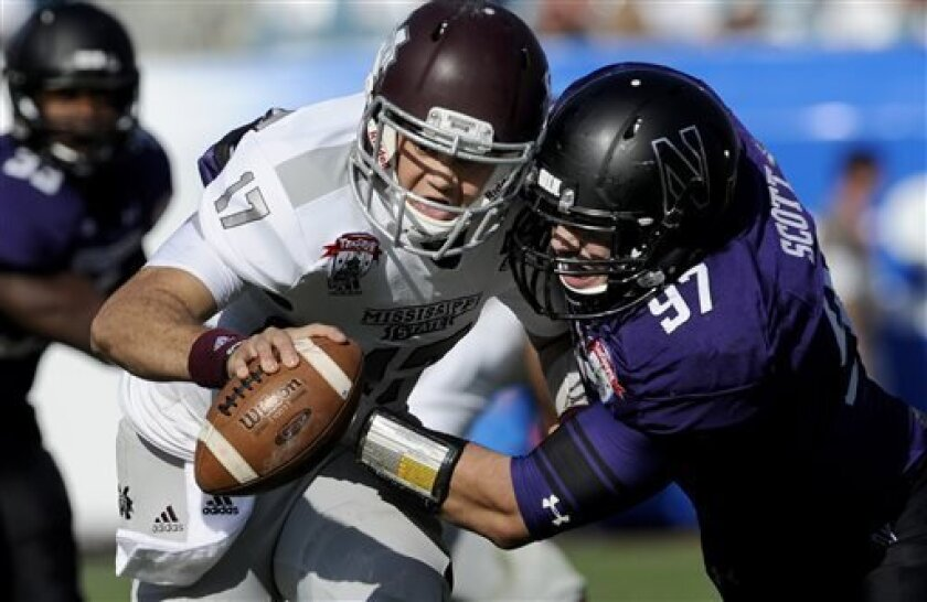 FILE - In this Jan. 1, 2013, file photo, Mississippi State quarterback Tyler Russell is sacked by Northwestern defensive lineman Tyler Scott (97) during the second half of the Gator Bowl NCAA college football game in Jacksonville, Fla. Northwestern would appear primed to make a run at the division title this fall, with eight starters returning on offense and seven on defense. (AP Photo/Stephen Morton, File)
