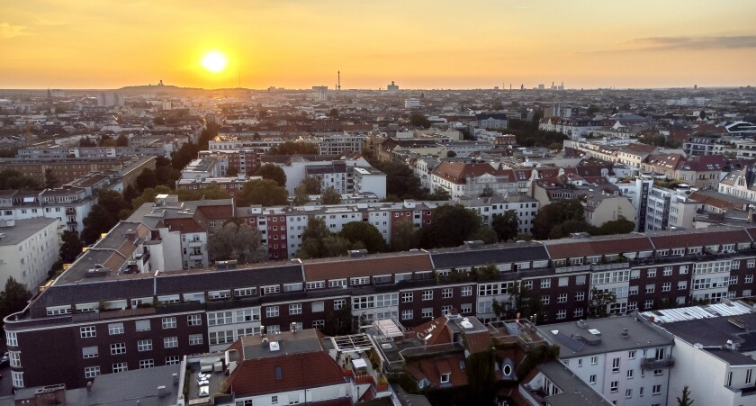 FILE - In this Sept. 7, 2021 file photo the sun goes down behind apartment houses in Berlin, Germany. Berlin's city government said Friday it is buying some 14,750 apartments from two large corporate landlords for 2.46 billion euros ($2.9 billion) — a deal announced a week before local and national elections as the German capital tries to expand the supply of publicly owned accommodation. (AP Photo/Michael Sohn, File)