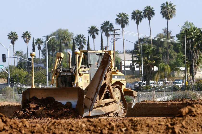 A bulldozer grades a section of property for the new Palomar Station project in San Marcos across from Palomar College. The project will includes 370 residences and nearly 50,000 square feet of retail on 15-acres of land.