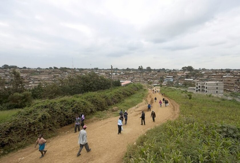 People walk toward the Nairobi slum of Kibera in Kenya in June. In Kibera, most mob attacks are carried out by young men in small vigilante groups who rely on informants.