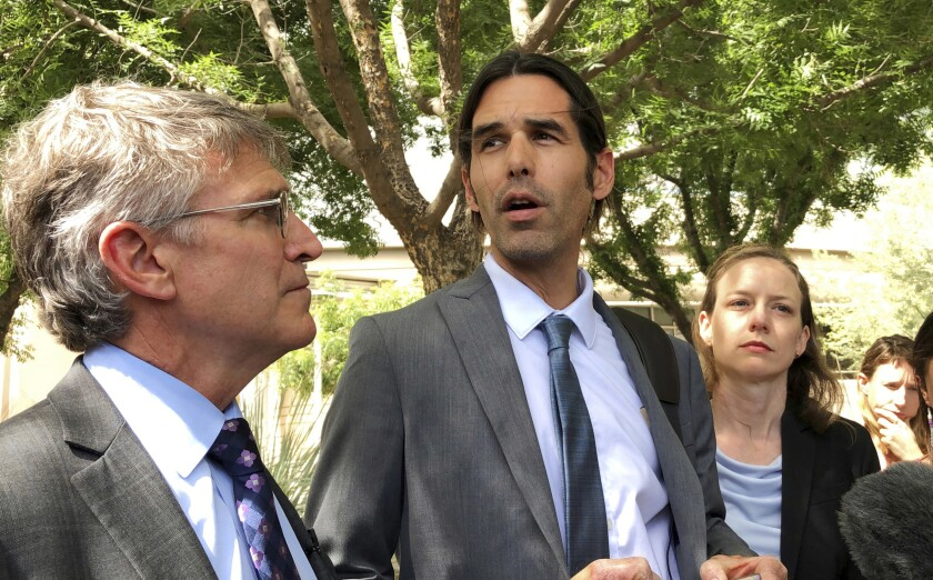 FILE - In this June 11, 2019, file photo, Scott Warren, center, speaks outside federal court, in Tucson, Ariz., after a mistrial was declared in the federal case against him. The second trial against Warren, a border activist accused of harboring immigrants in the country illegally, is set to start on Tuesday, Nov. 12, 2019. (AP Photo/Astrid Galvan, File)