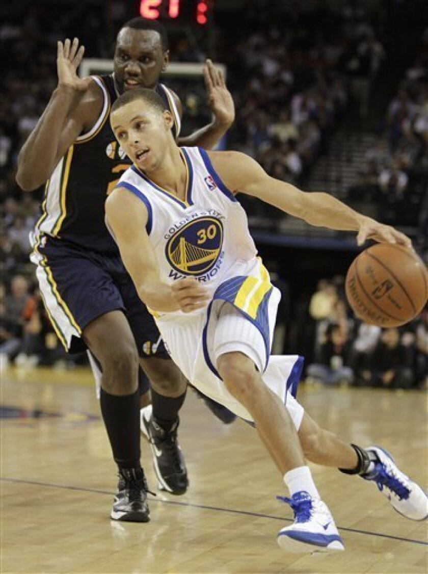 Golden State Warriors' Stephen Curry (30) drives past Utah Jazz forward Al Jefferson during the first half of an NBA basketball game Friday, Nov. 5, 2010, in Oakland, Calif. (AP Photo/Ben Margot)